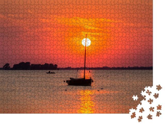 """Puzzle 1000 Teile """"Sonnenuntergang am Steinhuder Meer: Boot im roten Licht, Niedersachsen"""""""