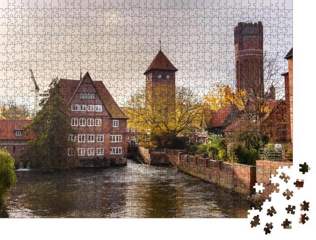 """Puzzle 1000 Teile """"Ratsmühle oder alte Wassermühle und Wasserturm an der Ilmenau, Lüneburg"""""""