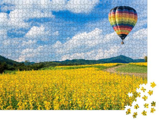 """Puzzle 1000 Teile """"Heißluftballon über gelben Blumenfeldern, im Hintergrund ein Mittelgebirge """""""