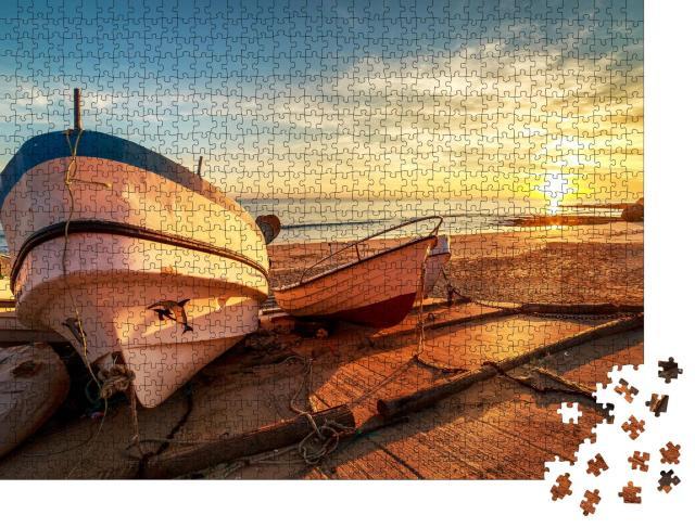 """Puzzle 1000 Teile """"Hölzerne Fischerboote in einem kleinen Hafen am Strand bei Sonnenuntergang"""""""