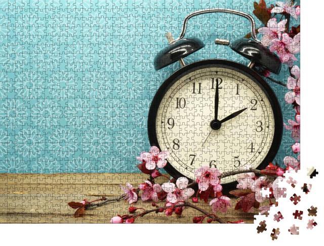 """Puzzle 1000 Teile """"Zeitumstellung im Frühjahr, Wecker auf Holz, blauer Hintergrund mit Blumen"""""""
