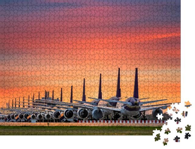 """Puzzle 1000 Teile """"Geparkte Flugzeugflotte am abendlichen Flughafen"""""""