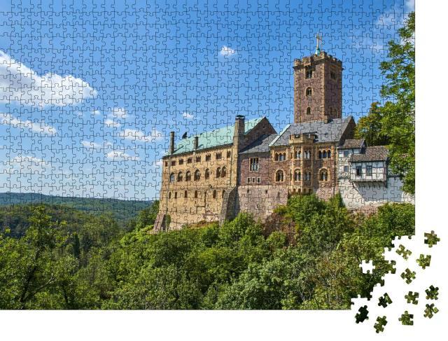"""Puzzle 1000 Teile """"Die Wartburg auf einem begrünten Hügel unter blauem Himmel und Sonnenlicht"""""""