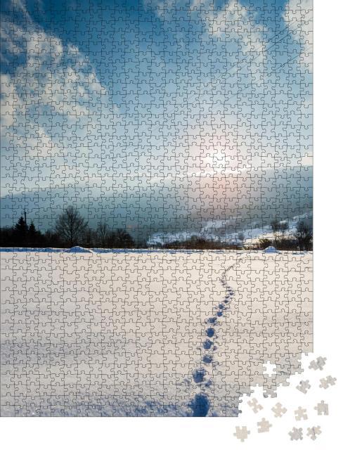 """Puzzle 1000 Teile """"Spuren im Schnee in den Sonnenuntergang"""""""